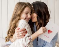 mother hugging daughter with greeting card 23 2148092257